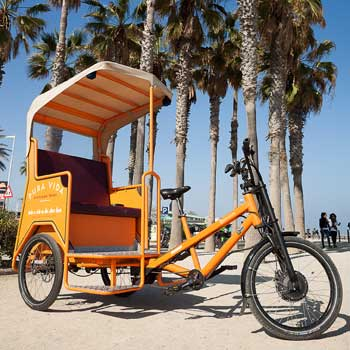 Pedicab on the beach with palms in Barcelona